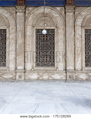 Three adjacent arched windows with decorated iron grid over white marble decorated wall at the Mosque of Muhammad Ali Pasha (Alabaster Mosque) Citadel of Cairo Egypt