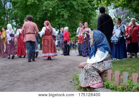 St. Petersburg Russia - May 22 2016: The girl in a national suit looks at dancing. An annual Nikolsky festival of folk art in St. Petersburg.
