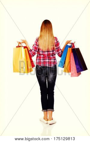 Back view of going woman with shopping bags