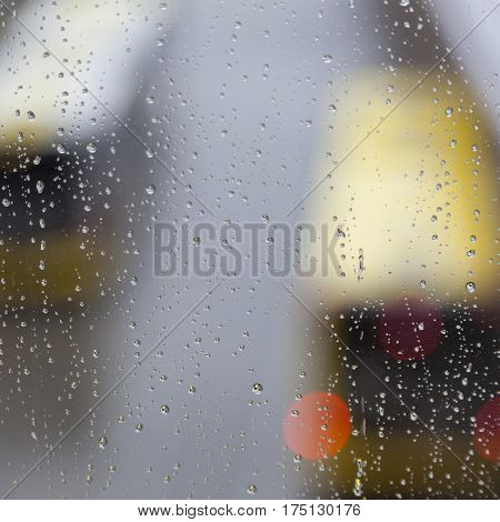 raindrops on glass pane and out of focus busses
