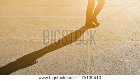 Silhouette of Man walking or stepping with shadow and sunlight on road.