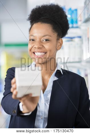 Cheerful Businesswoman Showing Medicine Box In Pharmacy