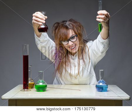 Happy scientist with glass flask on gray background