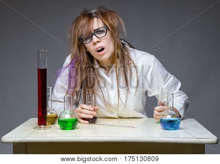 Scattered scientist with glass flask on gray background