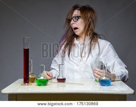 Problem and surprised scientist with glass flask on gray background