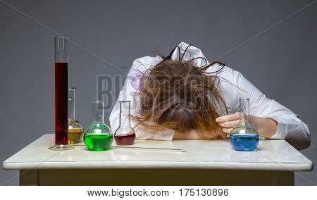 Tired scientist with glass flask on gray background