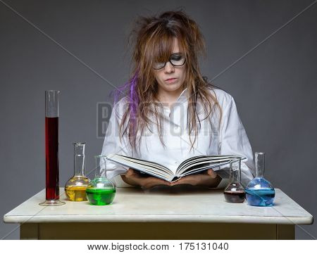 Reading scientist with glass flask on gray background