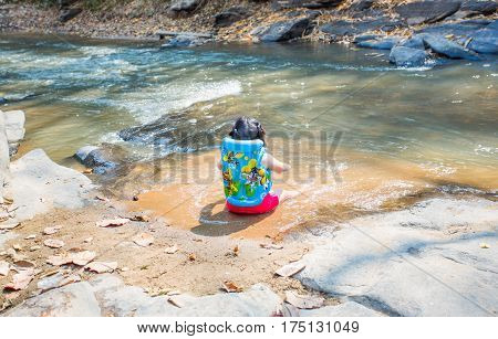 Little girl is soaking in stream, alone girl