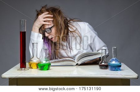 Reading tired scientist with glass flask on gray background