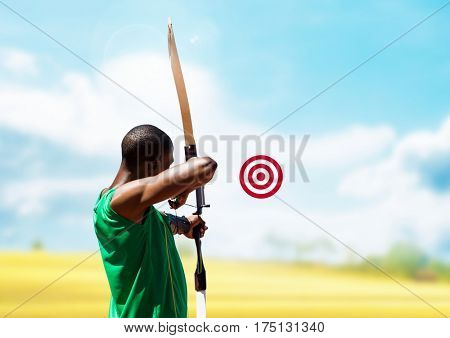 Digital composition of man aiming with bow and arrow at target in the sky