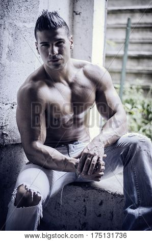 Muscular young latino man shirtless in jeans sitting against concrete wall looking at camera