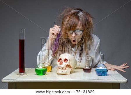 Working scientist with human skull on gray background