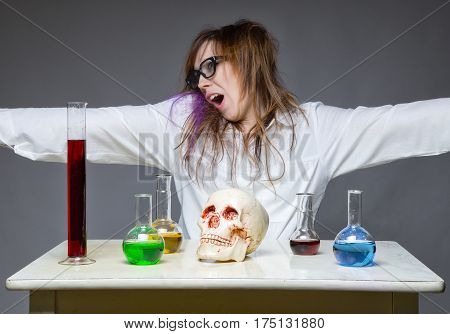 Yawning scientist with human skull on gray background