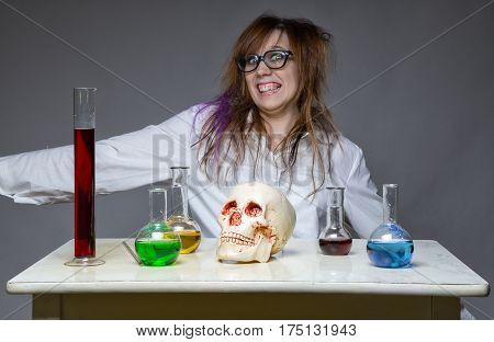 Happy smiling scientist with human skull on gray background