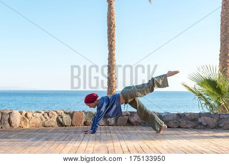 Woman doing yoga asana at pier of tourist resort