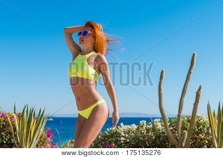 Cool Red Woman wearing yellow bikini doing fitness exercises at tourist resort