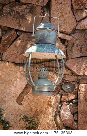 Old Antique Oil Lantern Hanging on a Stone Wall
