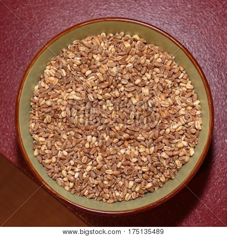 Top View Of Barley And Pearl Barley Inside Bowl On Red Table