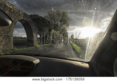 The arches of an aqueduct from dashboard of the car