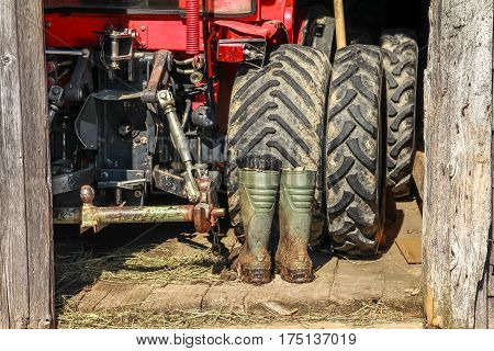 Red tractor and rubber boots in wooden barn. Half opened barn door allows view inside.