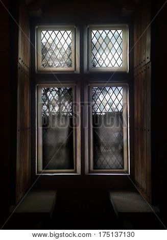 Old window with stained glass and wooden shutters