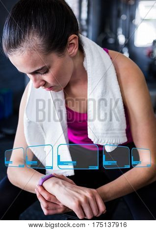 Digital composition of woman looking at fitness band on wrist in gym and fitness interface