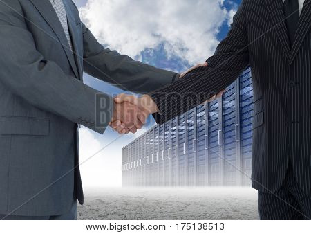 Digital composition of businessman shaking hands with each other and servers against sky in background