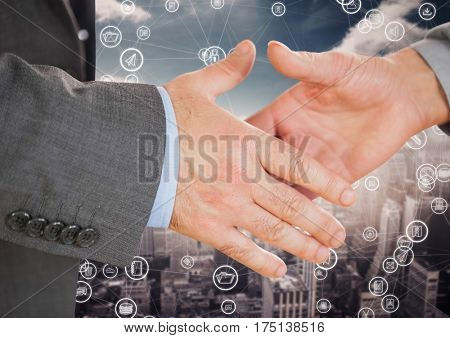 Close-up of businesspeople shaking hands against digitally generated background