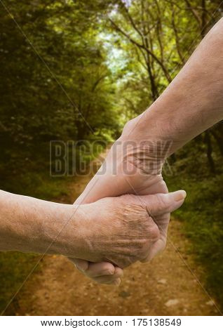 Digital composition of senior couple holding hands against footpath