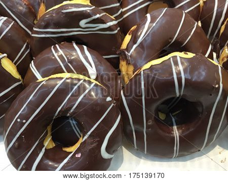 Display of delicious pastries in a bakery with assorted glazed donuts, on trays in a shop counter.