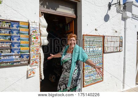 Alberobello Italy 21 June 2016: Woman in front of her souvenir shop of Alberobello Unesco world heritage on Puglia southern Italy