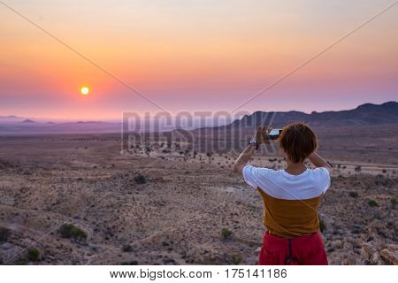 Tourist Photographing With Smartphone The Stunning View Of Barren Valley In The Namib Desert, Majest
