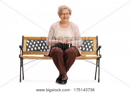 Mature woman with a book in her lap sitting on a bench and looking at the camera isolated on white background