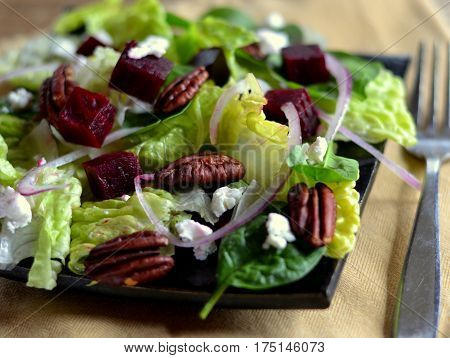Salad of Roasted Beets, Goat Cheese (Chevre) and Toasted Pecans. Salad also includes red onion, romaine lettuce and baby spinach.