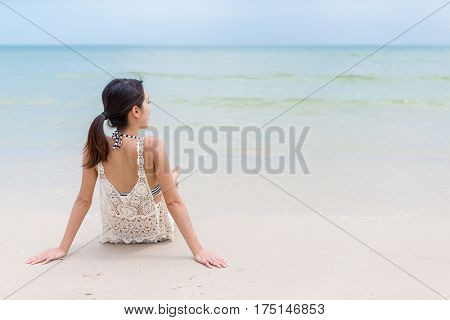 Woman sitting on the sand beach