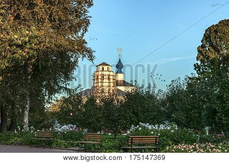 silent monastic garden with benches and flowers against the background of the restored Christian church in Pereslavl-Zalessky