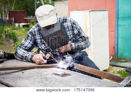 Aged man welding metal construction at his garden
