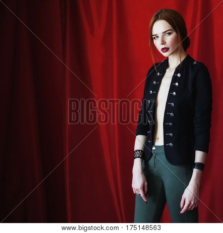 Beautiful red-haired girl in black unbuttoned jacket with bracelet on hand on red background looking at the camera in studio. Fashion photography in studio. Bright appearance. Red hair. Woman posing hands in studio