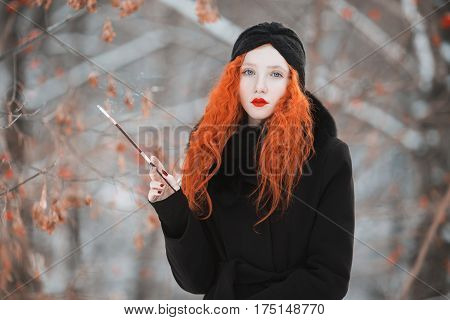 A woman lady with red hair in a black coat on background of a winter forest with a mouthpiece in hand. Red-haired lady girl with bright appearance with a turban on her head with a cigarette. Smoking aesthetics. Redhead lady