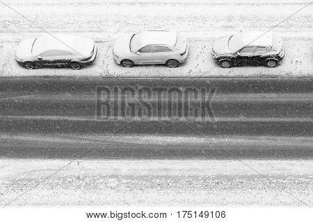 three cars under snowfall are parked on the winter road to one row along the sidewalk