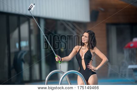 Close-up Portrait Of Attractive Smiling Woman In A Black Sexy Swimsuit, Taking Selfie Photo With Mon