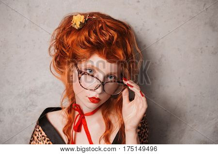 A woman with glasses and red hair in leopard print gown with glasses in hand. Red-haired in glasses girl with pale skin and blue eyes with a bright unusual appearance with a red ribbon around her neck. French courtesan with glasses