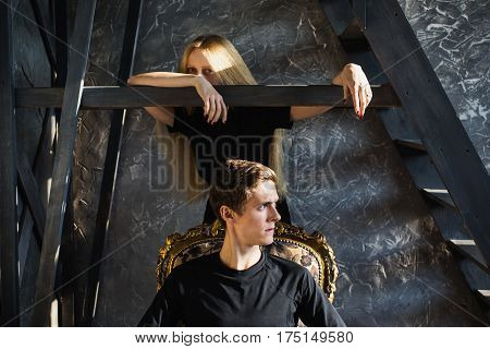 A young man and young blonde woman problem with long hair. Problems and difficulties in relations. Difficult problem situation in life. Conceptual photography. Actor play. Hard shadows. Show feelings. Hide feelings.