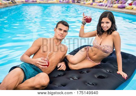 Happy Couple Relaxing With Cocktails On A Blue Inflatable Mattress At The Swimming Pool. Young Peopl