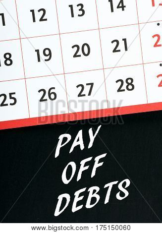 The words Pay Off Debts in white text on a blackboard with a calendar as a reminder of the date