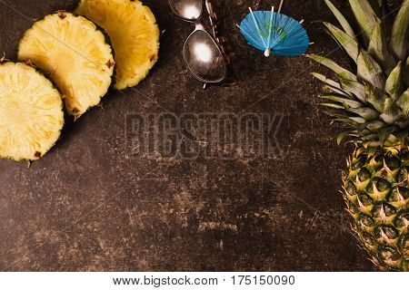 Ripe exotic pineapple and cocktail umbrellas leopard sunglasses on dark table with a marble texture with scratches. Cut exotic fruit. Healthy exotic eating. Going on a journey to the south. Flat lay top view. Copyspace