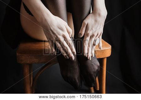 Women's hands with dark manicure lie on her feet. Dark nail polish. A woman sits on a chair