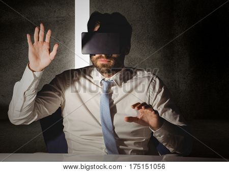 Man pretending to touch while wearing virtual reality headset at desk