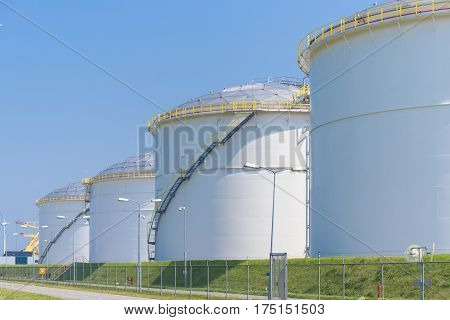 rows of large oil silos in the port of amsterdam