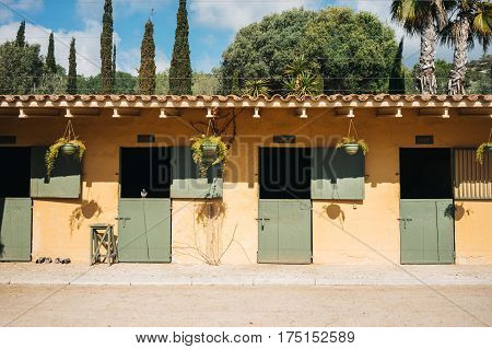 Empty stables for horses with yellow wall and green doors on ranch
